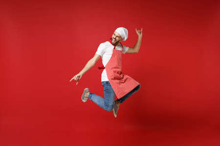 Crazy young male chef cook or baker man in striped apron toque chefs hat posing isolated on red background. Cooking food concept. Mock up copy space. Jumping, having fun, showing horns up gesture.