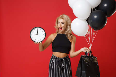 Excited young woman girl in black clothes posing isolated on red background studio portrait. Shopping discount sale concept. Mock up copy space. Holding air balloons package bag with purchases, clock. 版權商用圖片