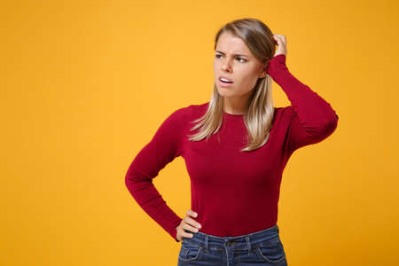 Preoccupied young blonde woman girl in casual clothes posing isolated on yellow orange wall background studio portrait. People lifestyle concept. Mock up copy space. Put hand on head, looking aside.