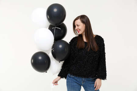Young woman girl posing celebrating holding black and white air balloons isolated on white wall background studio portrait. Birthday holiday party people emotions lifestyle concept. Mock up copy space