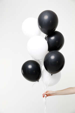 Close up cropped photo of female hold in hand bunch of black and white air balloons isolated on white wall background in studio. Birthday holiday party people lifestyle concept. Mock up copy space.