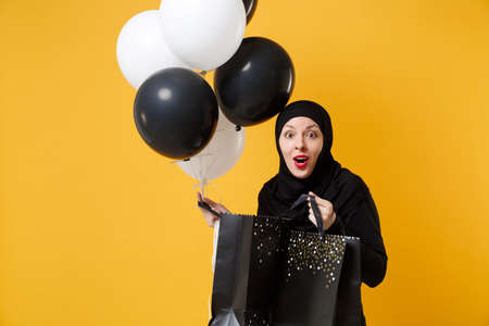 Arabian muslim woman in hijab celebrating holding black white air balloons isolated on yellow background studio portrait. Birthday holiday party people religious lifestyle concept. Mock up copy space.