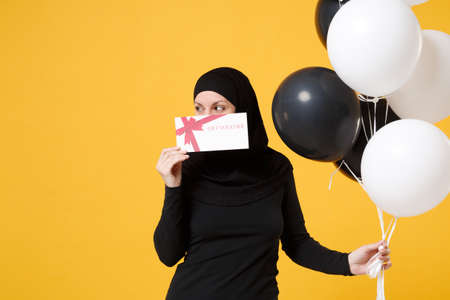 Arabian muslim woman in hijab celebrating hold voucher black white air balloons isolated on yellow background studio portrait. Birthday holiday people religious lifestyle concept. Mock up copy space.