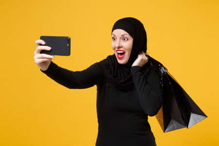 Arabian muslim woman in black hijab hold package bag, purchases shopping phone isolated on yellow background studio portrait. Birthday holiday people religious lifestyle concept. Mock up copy space. Stock Photo