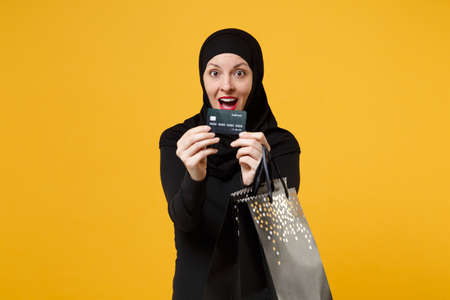 Arabian muslim woman in black hijab hold package bag, purchases shopping bank card isolated on yellow background studio portrait. Birthday holiday people religious lifestyle concept Mock up copy space