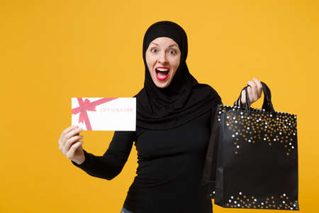 Arabian muslim woman in black hijab hold package bag, purchases shopping voucher isolated on yellow background studio portrait. Birthday holiday people religious lifestyle concept. Mock up copy space. Stock Photo