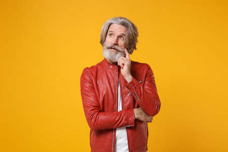 Pensive elderly gray-haired mustache bearded man in red leather jacket posing isolated on yellow orange background. People lifestyle concept. Mock up copy space. Put hand prop up on chin, looking up.