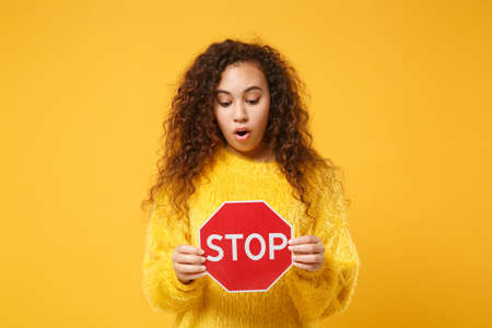Shocked young african american girl in fur sweater posing isolated on yellow orange wall background, studio portrait. People lifestyle concept. Mock up copy space. Holding red sign with Stop title. Standard-Bild