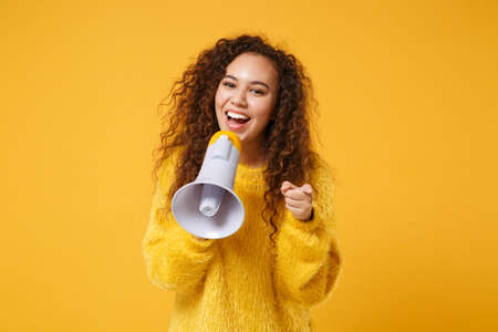 Funny young african american girl in fur sweater posing isolated on yellow orange wall background. People lifestyle concept. Mock up copy space. Scream in megaphone, pointing index finger on camera.