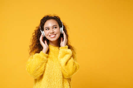 Pretty young african american girl in fur sweater posing isolated on yellow orange background in studio. People sincere emotions lifestyle concept. Mock up copy space. Listen music with headphones.