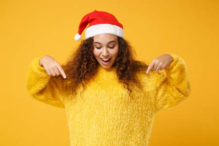 Excited young african american Santa girl in fur sweater, Christmas hat isolated on yellow background. Happy New Year 2020 celebration holiday concept. Mock up copy space. Pointing index fingers down.