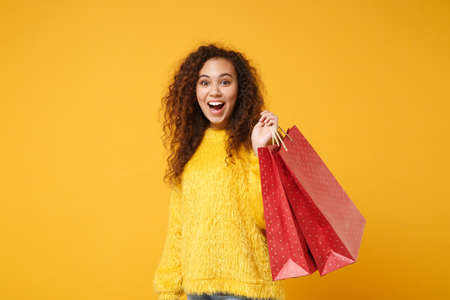 Surprised young african american girl in fur sweater posing isolated on yellow orange wall background. People lifestyle concept. Mock up copy space. Holding package bag with purchases after shopping. Stock Photo