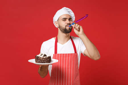 Cheerful male chef cook or baker man in striped apron white t-shirt toque chefs hat posing isolated on red background. Cooking food concept. Mock up copy space. Holding plate with cake, birthday pipe. Standard-Bild