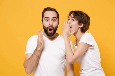 Shocked couple friends bearded guy girl in white t-shirts posing isolated on yellow orange background.