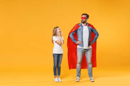 Bearded man in casual clothes costume with excited child baby girl. Father little kid daughter isolated on yellow background. Love family parenthood childhood concept. Stand with arms akimbo.