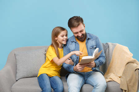 Funny bearded man in casual clothes with cute child baby girl. Father little daughter isolated on pastel blue background. Love family parenthood childhood concept. Sit on couch reading book hugging. Standard-Bild - 156217804