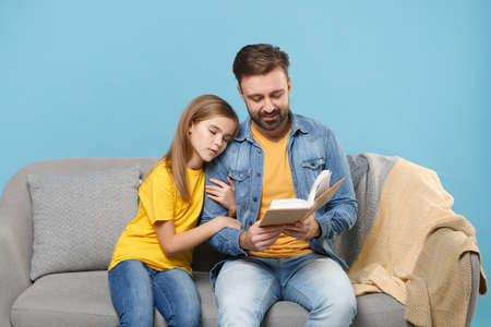 Pretty bearded man in casual clothes with cute child baby girl. Father little daughter isolated on pastel blue background. Love family parenthood childhood concept. Sit on couch reading book hugging.