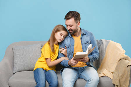 Smiling bearded man in casual clothes with cute child baby girl. Father little daughter isolated on pastel blue background. Love family parenthood childhood concept. Sit on couch reading book hugging. Banco de Imagens - 156217802