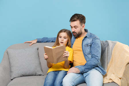 Shocked bearded man in casual clothes with cute child baby girl. Father little daughter isolated on pastel blue background. Love family parenthood childhood concept. Sit on couch reading book hugging. Banco de Imagens - 156217803