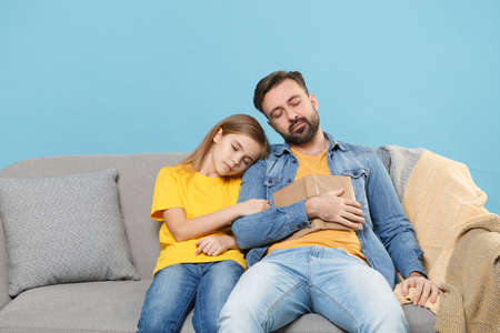 Relaxed bearded man in casual clothes with cute child baby girl. Father little daughter isolated on pastel blue background. Love family parenthood childhood concept. Sit on sofa reading book sleeping.