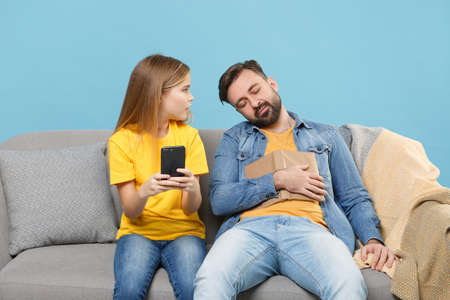 Bearded man in casual clothes with child baby girl. Father little daughter isolated on pastel blue background. Love family parenthood childhood concept. Sit on sofa hold book mobile phone sleeping. Standard-Bild
