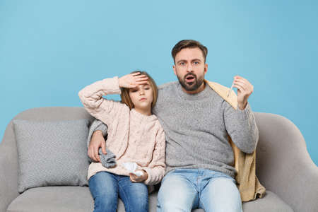 Bearded man in knitted sweater with sick tired child baby girl. Father little daughter isolated on blue background. Love family parenthood childhood concept. Sitting on couch hold napkin, thermometer. Banco de Imagens - 156217818
