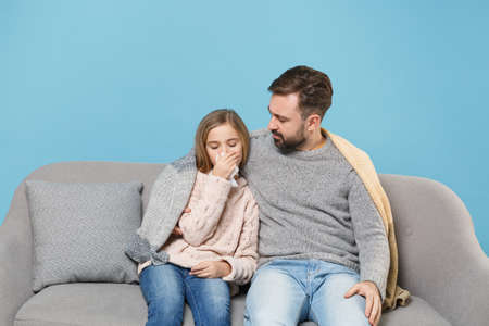 Man in knitted sweater with sick child baby girl. Father little daughter isolated on blue background. Love family parenthood childhood concept. Sit on couch, having runny nose, blowing nose to napkin. Standard-Bild - 156217816