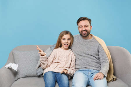 Cheerful bearded man in knitted sweater with child baby girl. Father little daughter isolated on pastel blue background. Love family parenthood childhood concept. Sitting on couch, spreading hands. Banco de Imagens - 156217817
