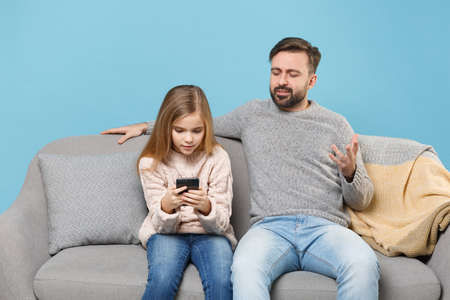 Bearded man in knitted sweater with cute child baby girl. Father little daughter isolated on pastel blue background. Love family parenthood childhood concept. Sitting on couch, hold mobile phone. Banco de Imagens - 156217665