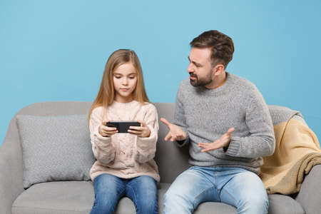 Nervous bearded man in knitted sweater with child baby girl. Father little daughter isolated on pastel blue background. Love family parenthood childhood concept. Sitting on couch, hold mobile phone. Banco de Imagens - 156217667