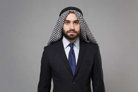 Bearded young arabian muslim businessman in keffiyeh kafiya ring igal agal classic black suit shirt tie posing isolated on gray background studio portrait. Achievement career wealth business concept.