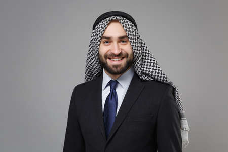 Smiling young bearded arabian muslim businessman in keffiyeh kafiya ring igal agal classic black suit shirt tie isolated on gray background. Achievement career wealth business concept. Looking camera. Banco de Imagens - 156217671