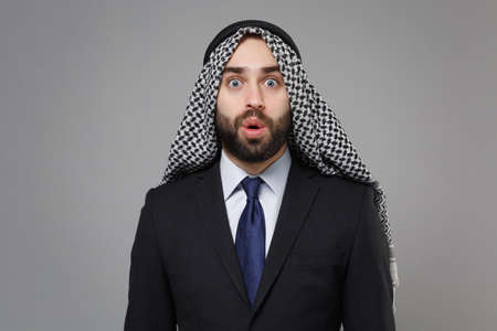 Shocked young bearded arabian muslim businessman in keffiyeh kafiya ring igal agal classic black suit shirt isolated on gray background. Achievement career wealth business concept. Keeping mouth open.