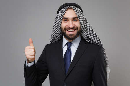 Smiling young bearded arabian muslim businessman in keffiyeh kafiya ring igal agal classic black suit shirt isolated on gray background. Achievement career wealth business concept. Showing thumb up.