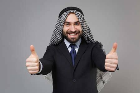 Smiling young bearded arabian muslim businessman in keffiyeh kafiya ring igal agal classic black suit shirt isolated on gray background. Achievement career wealth business concept. Showing thumbs up.