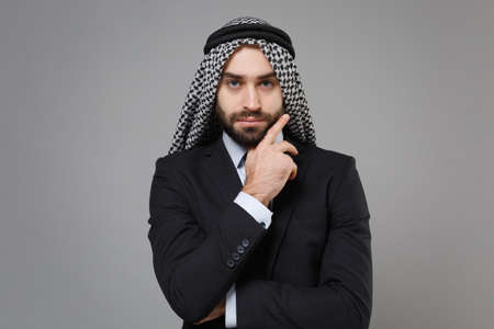 Confident bearded arabian muslim businessman in keffiyeh kafiya ring igal agal classic black suit isolated on gray background. Achievement career wealth business concept. Put hand prop up on chin.