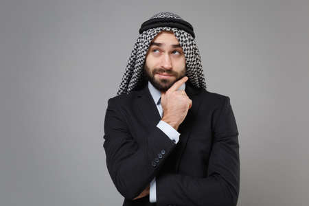Pensive bearded arabian muslim businessman in keffiyeh kafiya ring igal agal classic black suit shirt isolated on gray background. Achievement career wealth business concept. Put hand prop up on chin. Standard-Bild
