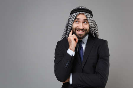 Smiling bearded arabian muslim businessman in keffiyeh kafiya ring igal agal classic black suit shirt isolated on gray background. Achievement career wealth business concept. Put hand prop up on chin. Standard-Bild