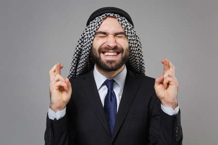 Arabian muslim businessman in keffiyeh kafiya ring igal agal isolated on gray background. Achievement career wealth business. Wait for special moment, keeping fingers crossed, eyes closed, make wish. Standard-Bild