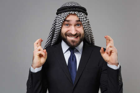 Arabian muslim businessman in keffiyeh kafiya ring igal agal isolated on gray background. Achievement career wealth business. Wait for special moment keeping fingers crossed, biting lips, making wish. Standard-Bild - 156217680