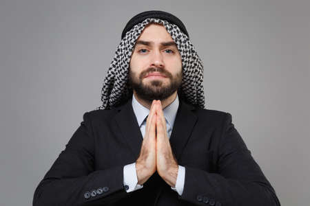 Bearded arabian muslim businessman in keffiyeh kafiya ring igal agal classic black suit shirt isolated on gray background. Achievement career wealth business concept. Holding hands folded in prayer. Banco de Imagens - 156217681