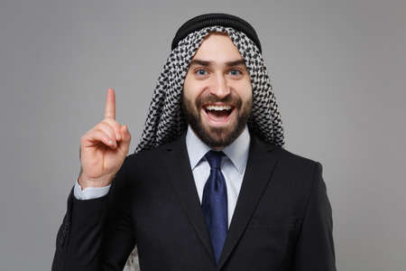 Bearded arabian muslim businessman in keffiyeh kafiya ring igal agal classic black suit isolated on gray background. Achievement career wealth business concept. Holding index finger up with new idea.