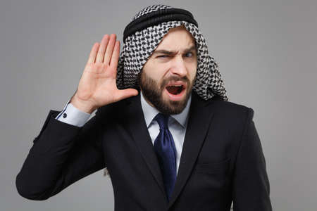 Curious arabian muslim businessman in keffiyeh kafiya ring igal agal classic black suit isolated on gray background. Achievement career wealth business concept. Try to hear you with hand near ear. Banco de Imagens