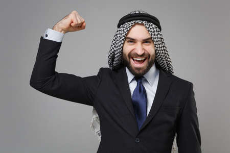 Strong bearded arabian muslim businessman in keffiyeh kafiya ring igal agal classic black suit tie isolated on gray background. Achievement career wealth business concept. Showing biceps, muscles.