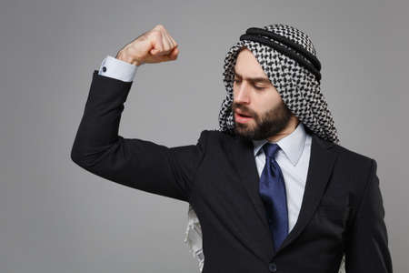 Strong bearded arabian muslim businessman in keffiyeh kafiya ring igal agal classic black suit tie isolated on gray background. Achievement career wealth business concept. Showing biceps, muscles. Banco de Imagens - 156217581