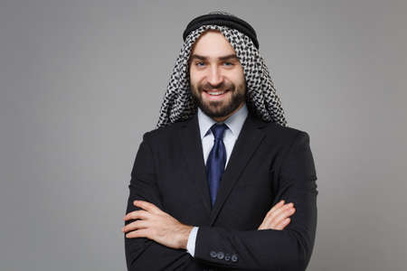 Smiling young bearded arabian muslim businessman in keffiyeh kafiya ring igal agal classic black suit tie isolated on gray background. Achievement career wealth business concept. Hold hands crossed.