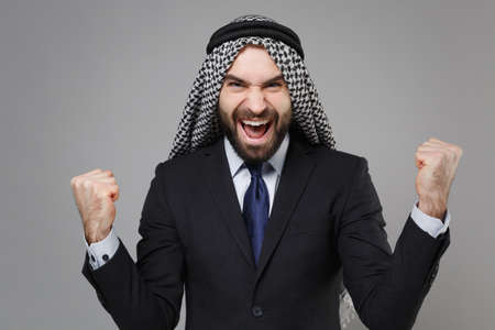 Happy young bearded arabian muslim businessman in keffiyeh kafiya ring igal agal classic black suit tie isolated on gray background. Achievement career wealth business concept. Doing winner gesture.