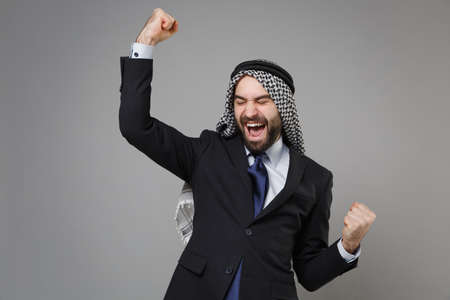 Joyful bearded arabian muslim businessman in keffiyeh kafiya ring igal agal classic black suit tie isolated on gray background. Achievement career wealth business concept. Clenching fists like winner. Standard-Bild - 156217585