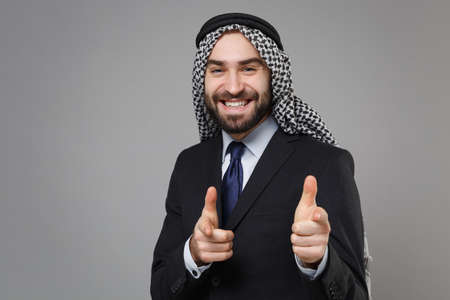Smiling bearded arabian muslim businessman in keffiyeh kafiya ring igal agal classic black suit isolated on gray background. Achievement career wealth business concept. Point index fingers on camera. Standard-Bild - 156217588
