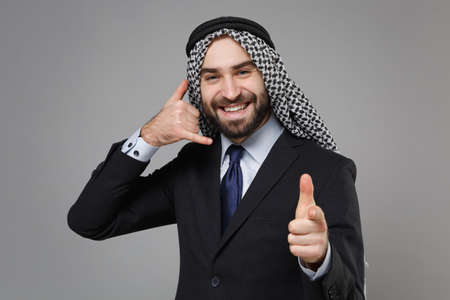 Smiling arabian muslim businessman in keffiyeh kafiya ring igal agal classic black suit isolated on gray background. Achievement career wealth business concept. Doing phone gesture says call me back. Standard-Bild - 156217589